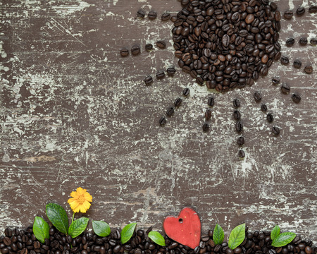 Sun shaped coffee beans and ground full of coffee with green leaves, yellow flower and shape of heart Stock Photo