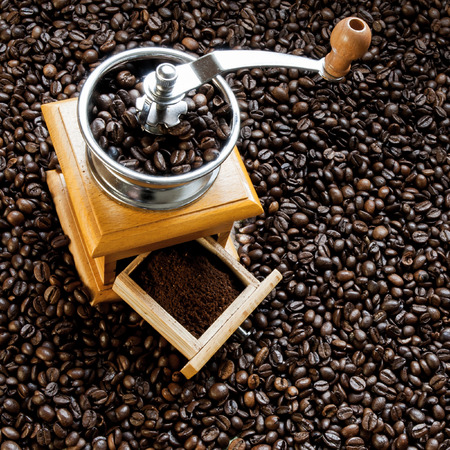 Old coffee mill on coffee beans background