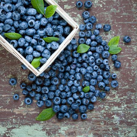 Freshly picked juicy blueberries in basket on wooden background Stock Photo