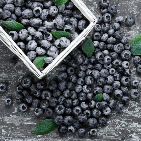 Blueberries in basket on old wooden table