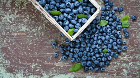 Wooden basket full of fresh blueberries on table