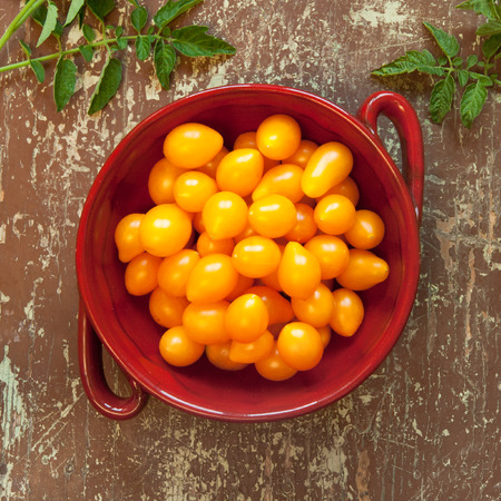 Bowl of sweet yellow pear shaped tomatoes on a rustic wooden table Stock Photo