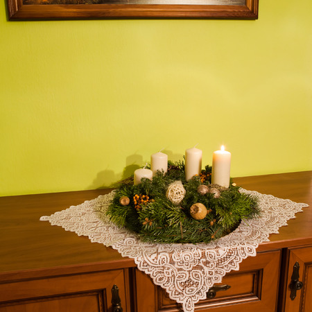 Advent wreath on rustic furniture with white tablecloth Stock Photo