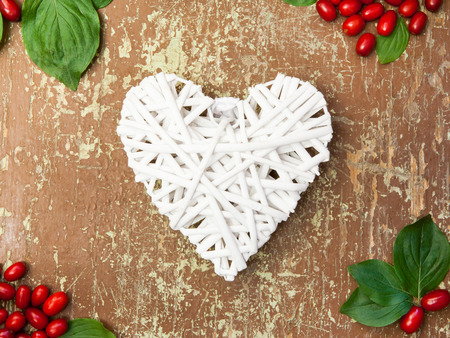 Freshly picked berries and white shape of heart