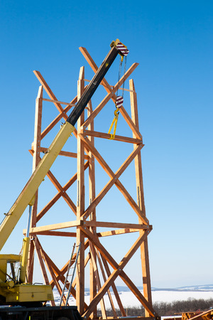 Mobile crane is building a wooden tower with clear blue sky on background