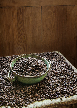 Clay bowl full of fresh roasted coffee beans