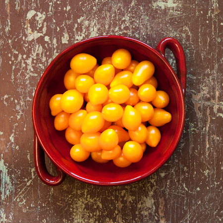 Pear shaped tomatoes in a clay bowl on a rustic wooden table