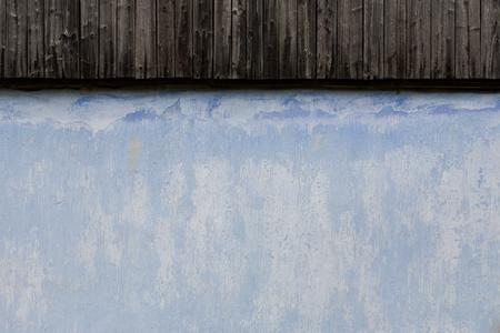 Oberfläche der alten Hauswand mit historischen Gemälden von blauer Farbe und einem Teil des Holzdachs