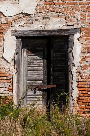 Gebrochene hölzerne Eingangstür eines alten Backsteinhauses Lizenzfreie Bilder