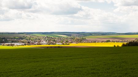 Dorf umgeben von fruchtbaren Feldern und einem bewölkten Himmel über Lizenzfreie Bilder