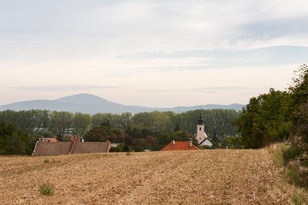 Blick auf Kirche und Dächer von Landhäusern in einem kleinen Dorf