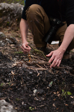 Man hands burning dry branches to start a campfire in the wild Lizenzfreie Bilder