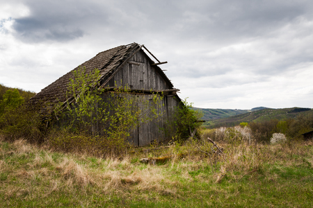 damaged roof: Rural West Slovakia countryside with abandoned barn and farmland Stock Photo