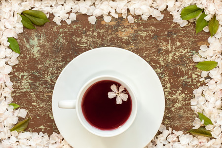 White cup of cherry tea and flowers petals on wooden background
