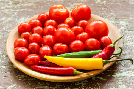 Tiny tomatoes and peppers in a wooden plate. Raw foods background close up