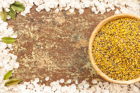 Honey bee pollen in a bowl on a rustic wooden table. Frame for text with flower petals and green leaves