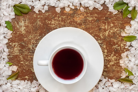 Red fruit tea in a white cup with frame of flower petals