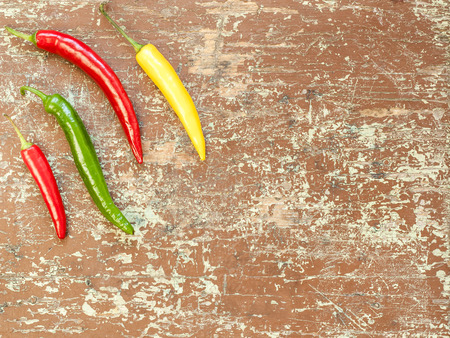 Top view of chili peppers of different color on wooden table background