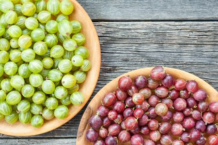 Green and red ripe gooseberries in a bowl on wooden table. Juicy berries background.