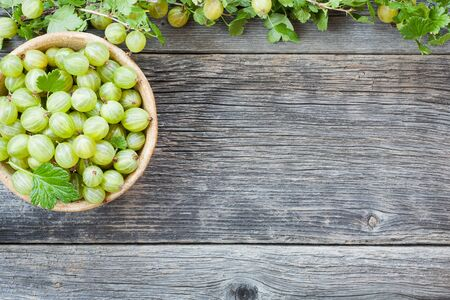 Ripe fresh green gooseberries on the wooden table. Healthy summer raw food background Stock Photo
