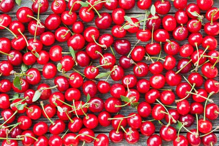 Juicy cherries scattered on a wooden background. Organic fresh fruits ready for eating Фото со стока
