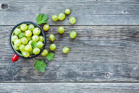 Gooseberries from a garden decorated with green leaves on a wooden board