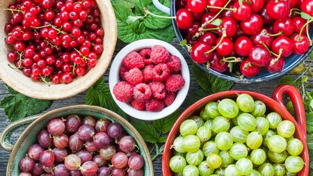 Assorted berries of gooseberry, currant, raspberry and cherry. Healthy summer raw food eating background Stock Photo