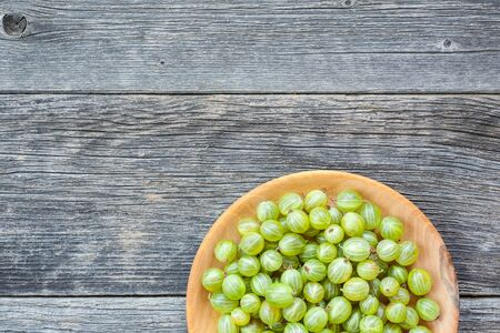 Juicy and ripe green gooseberries in a small round wooden plate