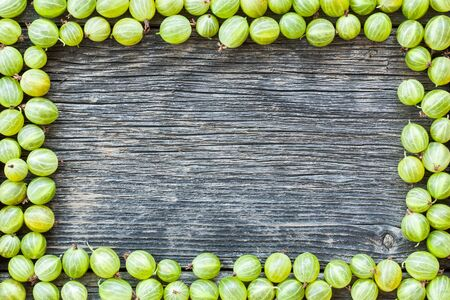 Closeup of ripe green gooseberries in a frame on wooden background