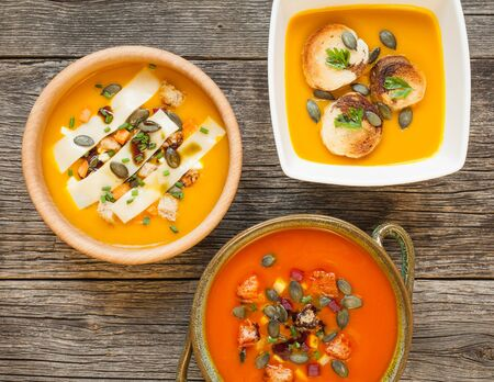 Hokkaido pumpkin soup with ingredients in bowls on rustic wooden background