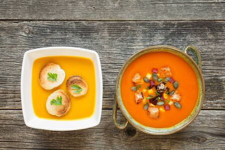 Pumpkin soup with ingredients in bowls on rustic background. Top view of healthy summer food