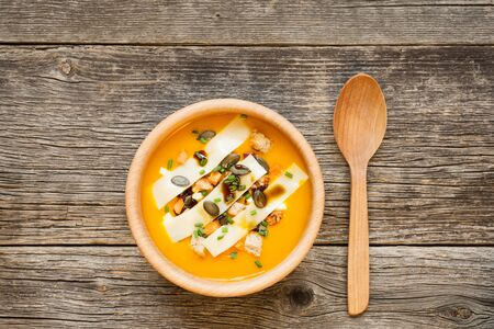 Closeup of pumpkin soup in wooden bowl on a rustic wooden table. Fresh and healthy summer food