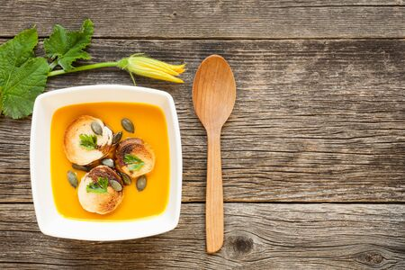 Hokkaido pumpkin soup in a white ceramic bowl decorated by leaves Stock Photo