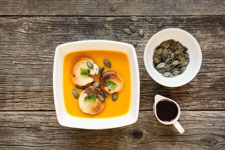 Bowl of hokkaido soup on wooden background. Pumpkin oil, seeds and tasty cream soup served with croutons