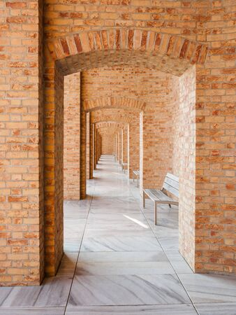 Long corridor with brick walls and arches. In separate spaces there are benches to relax