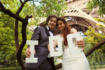Bride and groom holding I DO letters in their hand near Eiffel tower photo