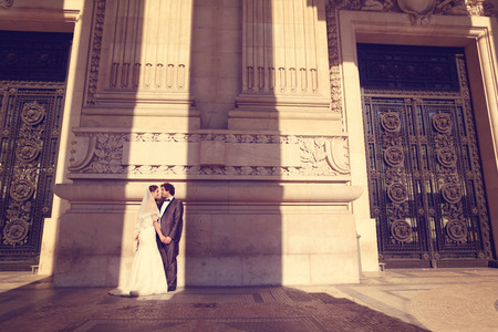 Bride and groom in front of a big building photo