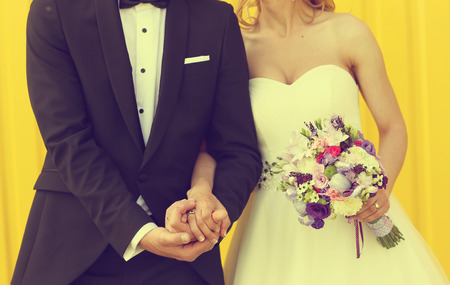 Bride and groom on a yellow background 版權商用圖片