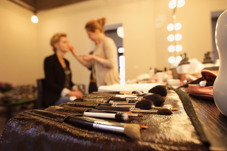 Stylist applying make up for bride on the wedding day with focus on the brushes Standard-Bild