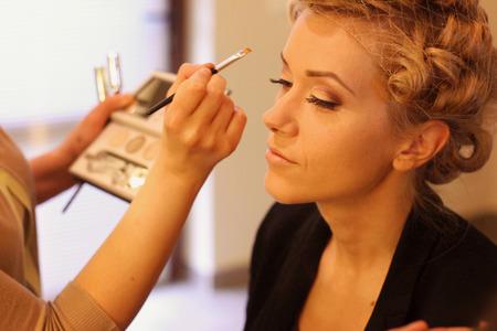 Stylist het aanbrengen van make-up voor de bruid op de trouwdag Stockfoto