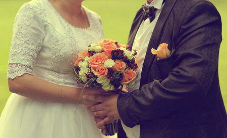 Bride holding her wedding bouquet made of roses photo