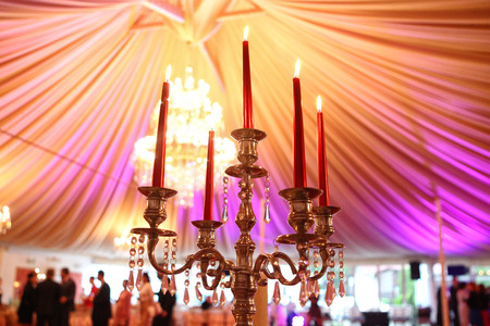 Ancient candle sticks and a chandelier on a wedding day photo
