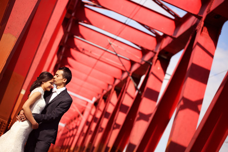 Bride and groom celebrating on a red bridge photo