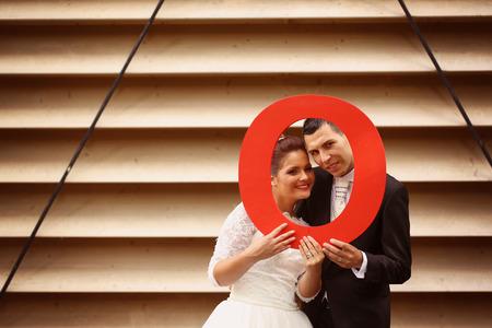 puja: Novia y el novio la celebración de una oferta letra O rojo Foto de archivo
