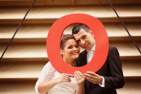 bid: Novia y el novio la celebración de una oferta letra O rojo Foto de archivo