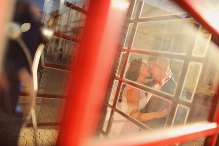 phonebooth: Bride and groom having fun near phonebooth