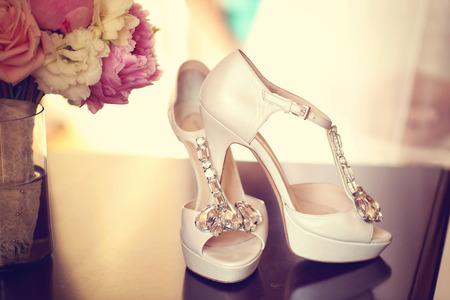 mariage: Elegant brides shoes with a peonies bouquet Banque d'images