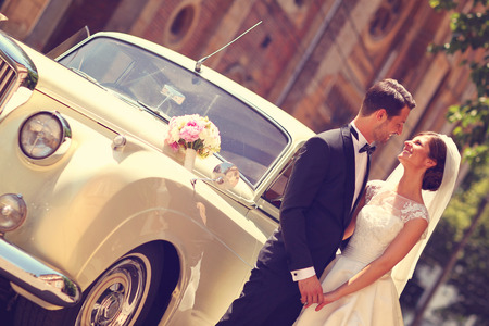 vow: Bride and groom with a retro car Stock Photo