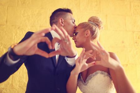 making love: Bruide y el novio haciendo el signo de amor con sus manos