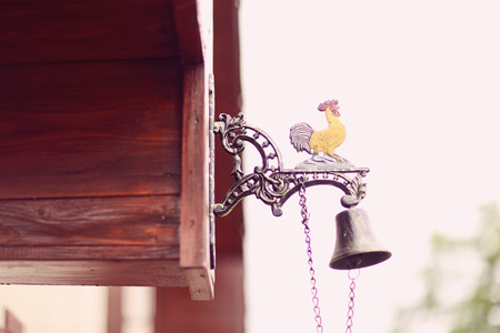 singing bells: Bell hanging on house with cockrell Stock Photo